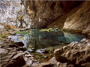 Вода «живого» озера у входа в Капову пещеру при свете дня кажется ярко-голубой