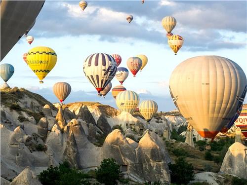 Воздушные шары то поднимаются в небо, то опускаются в ущелья, за счет мастерства пилотов пролетая в считаных сантиметрах от скал