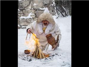 Якутский шаман проводит обряд очищения огнем