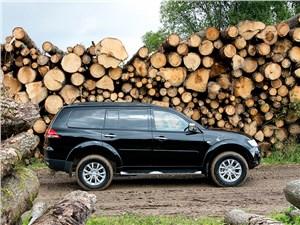 Mitsubishi Pajero Sport 2013 вид сбоку возле дров